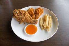 炸鸡腿和炸薯条在白色颜色板材 免版税图库摄影