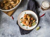 炸鸡飞过与石灰、辣椒和香菜在一块白色板材,低度黄啤酒在玻璃和在一个白色陶瓷烘烤盘子在gr 免版税库存照片