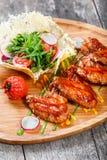 炸鸡飞过用新鲜的沙拉、烤菜和bbq调味汁在切板在木背景 免版税库存图片