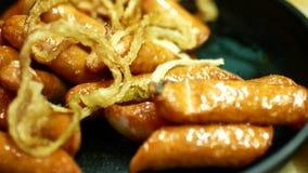 炸鸡香肠用葱在煎锅片 油腻的食物是酒精的一顿快餐 股票视频