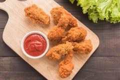 炸鸡鼓槌和番茄酱在木桌上 免版税图库摄影