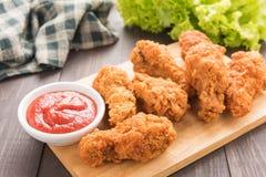 炸鸡鼓槌和菜在木背景 免版税库存照片