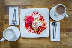 点心冰淇凌草莓绉纱和热的饮料在咖啡店 库存图片