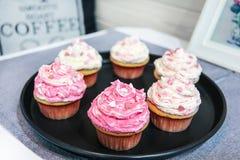 点心华伦泰与用甜心装饰的桃红色和白色奶油的香草杯形蛋糕 免版税库存照片
