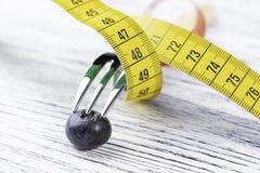 点心叉子包裹与一黄色厘米在一张白色木桌上的一个蓝莓站立 免版税库存照片