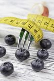 点心叉子包裹与在一张白色木桌上的黄色厘米用疏散蓝莓 免版税库存图片