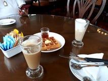 点心和咖啡在桌上与一部分的人身体 免版税库存图片