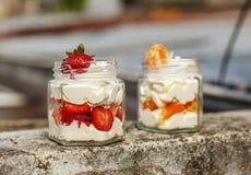点心奶油用草莓和普通话在瓶子 免版税库存图片