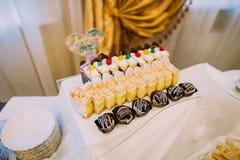 点心婚礼酒吧 在婚礼桌集合的不同的鲜美蛋糕 免版税库存图片