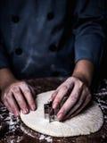 点心师切开模子的手用途切在厨房的曲奇饼面团 免版税库存照片