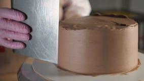 点心师妇女抹上在松糕的巧克力奶油与在转动的蛋糕立场的金属小铲在面包店 股票录像