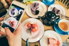 点心甜点制表与手机的流动食物照片 咖啡馆台式视图 库存照片