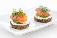 点心用乳酪、黄瓜和盐味的三文鱼在白色板材 库存图片