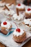 点心用巧克力沫丝淋和打好的奶油用樱桃在t 免版税库存图片