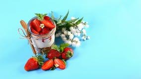 点心用新鲜的草莓,在玻璃的乳脂干酪果酱与夏天在蓝色背景开花 与拷贝空间的顶视图图象 库存图片