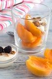 点心用桃子、奶油和莓 在一块玻璃的桃子与被鞭打的奶油和核桃 免版税图库摄影