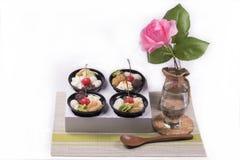 点心用红色莓果和绿茶奶油与美丽的桃红色玫瑰在白色背景 库存图片