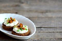 点心用软干酪和蘑菇在一块板材在木背景与拷贝空间文本的 免版税库存照片