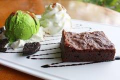 点心由果仁巧克力和绿茶冰淇凌制成与打好的奶油一起在白色板材 免版税图库摄影