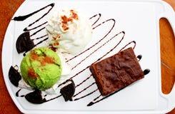 点心由果仁巧克力和绿茶冰淇凌制成与打好的奶油一起在白色板材 库存图片