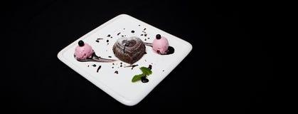 点心fondan巧克力用在一块白色板材的冰淇凌在黑背景 fondan精妙的法国巧克力的点心,地方f 免版税库存照片