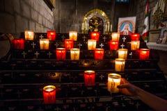 点燃一个蜡烛的手在教会里 图库摄影
