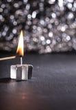 点燃与比赛的一个银色蜡烛 免版税图库摄影