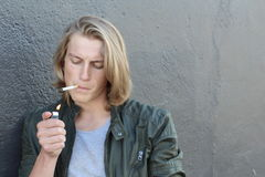 点燃与许多的年轻人一个香烟特写镜头拷贝空间 免版税库存照片