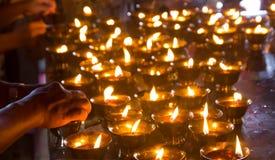 点燃在寺庙的妇女手蜡烛 免版税库存照片