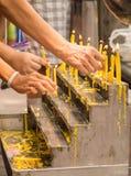 点燃在法坛的蜡烛的佛教徒的手支付他们 图库摄影