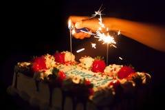 点燃在生日蛋糕闪耀 库存图片