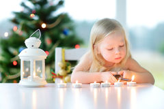 点燃在白色灯笼的美丽的小女孩一个蜡烛 图库摄影