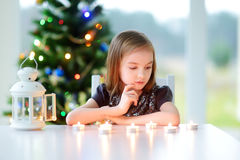 点燃在白色灯笼的美丽的小女孩一个蜡烛 免版税库存照片