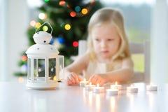 点燃在白色灯笼的美丽的小女孩一个蜡烛 免版税图库摄影