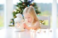 点燃在白色灯笼的美丽的小女孩一个蜡烛 库存图片