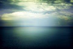 点燃在黑暗的阴沉的海上的天空 免版税库存照片