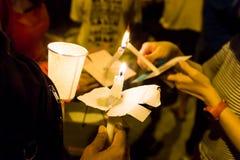 点燃在黑暗寻找的希望,崇拜的人们蜡烛守夜, 免版税库存图片