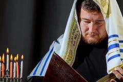 点燃在menorah的男性手蜡烛在桌光明节上 免版税库存照片