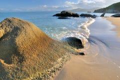 点燃岩石海运日落的海岸在温暖之下 库存图片
