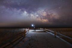 点燃海滩道路的人作为银河起来 库存照片