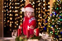 点燃蜡烛的小女孩在圣诞晚餐 免版税图库摄影