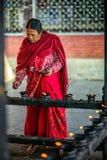 点燃蜡烛的年长妇女在祷告前在加德满都,国家环境政策法案 免版税库存照片