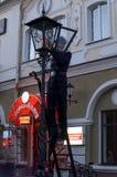 点燃街灯的灯夫光 库存照片