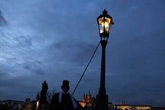 点燃街灯的灯夫在P的查理大桥点燃街道瓦斯灯 库存图片