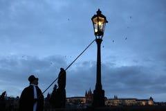 点燃街灯的灯夫在P的查理大桥点燃街道瓦斯灯 免版税图库摄影