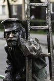 点燃街灯的灯夫雕象  免版税图库摄影