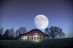 点燃被绘的谷仓在与满月和一些个星的夜间期间在背景 免版税库存图片