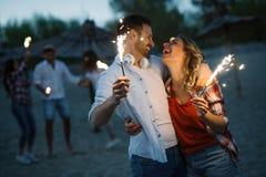点燃闪烁发光物和享受自由的愉快的小组朋友 库存图片
