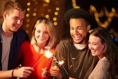 点燃闪烁发光物的小组朋友在室外党 库存照片
