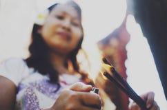 点燃香火棍子的巴厘语妇女 免版税图库摄影